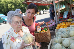 caregiver assisting senior woman to buy fruits